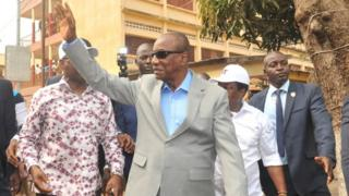 Guinea President Alpha Conde of Guinea dey wave after im cast vote on February 4, 2018 outside one polling station for Conakry
