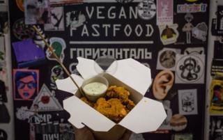 A box of tofu-seitan nuggets being held up in front of the sign for Horizontal