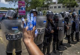 Nicaraguan women protest in front of riot police during a demonstration in Managua on 2 May 2018