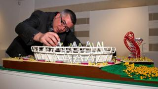 Warren Elsmore puts the finishing touches to his Lego version of the Olympic Park in London
