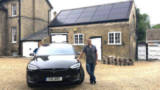 Adam Courtney standing next to Tesla car in front of house will solar panels