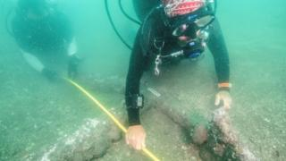 An underwater image of marine archaeologists take measurements of the anchors that date back to the 16th century