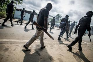 Gabonese police forces patrol as they clear barricades in the streets adjacent to the National Assembly, in Libreville