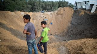 Palestinian children stand next to a crater on 22 August 2016 in Beit Lahia in the northern Gaza Strip