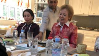 Sheikha Latifa is photographed alongside Mary Robinson being served at a table
