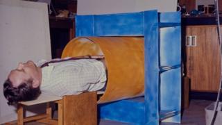 Sir Peter Mansfield inside a cardboard tube