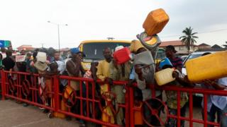 People wey queue for fuel.