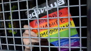 Detained gay rights activist in Moscow with sign saying 'love is stronger than homophobia', 25 May 13