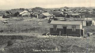 Black and white photo shows chalets among the sand dunes