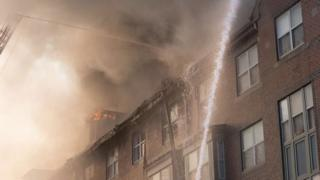 water hose sprays onto burning building