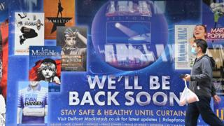 "Man walking past theatre poster saying ""We'll be back soon"" outside the Sondheim Theatre in London"