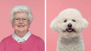 A woman with a bright smile and grey glasses looks forward next to a fluffy white dog which looks like its smiling