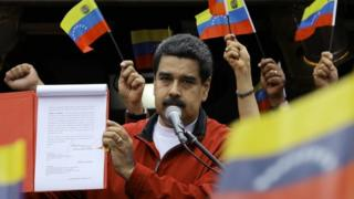 "Venezuela's President Nicolas Maduro shows a document with the details of a ""constituent assembly"" to reform the constitution during a rally at Miraflores Palace in Caracas, Venezuela May 23, 2017."