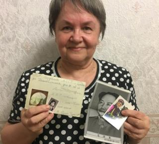 Lyudmila Mitricheva, holding up a letter written in Russian and a photo of her Chinese pen pal