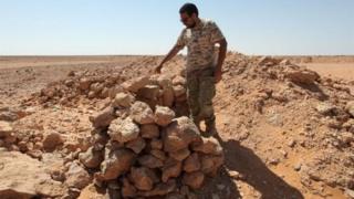"""Сотрудник ливийских сил безопасности на месте бывшего лагеря так называемого """"Исламского государства"""""""