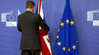 A man adjusts a UK flag ahead of press conference in Brussels