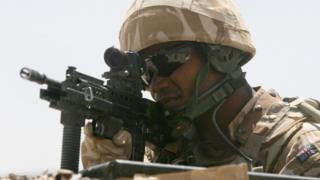 A British soldier looking through a gun sight