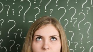 Mulher com vários pontos de interrogação no quadro