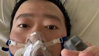 Dr Li posts a picture of himself in a gas mask from his hospital bed on Friday