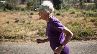 Deirdre Larkin, 86, is seen running in a purple T-shirt.