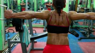 Женщина занимается на тренажерах