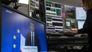 Screen showing Macron on a trading floor