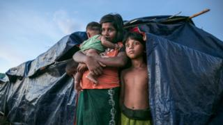 A Rohingya refugee family stands by their makeshift home in Bangladesh