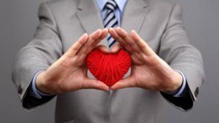 Homem de terno segura coração feito com novelo de linha