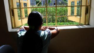 looking out from a window at a centre for trafficked women in the northern city of Lao Ca