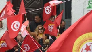 متظاهرون يحملون الاعلام التونسية