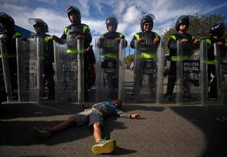 A six-year-old migrant boy lies on the floor in front of Mexican riot police