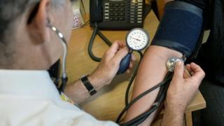 GP taking someone's blood pressure