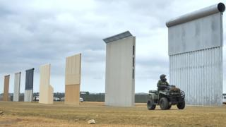 border-officer-looking-at-prototypes-of-the-wall.