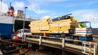 Timber on a lorry being loaded into a ship