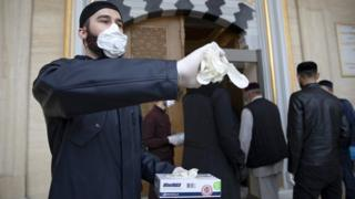 in_pictures Volunteers in face masks hand out gloves at the entrance to the Heart of Chechnya Mosque in Grozny, Chechen Republic