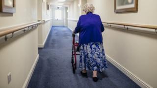 Elderly woman walking down a corridor