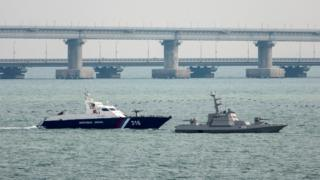A seized Ukrainian ship is towed by a Russian Coast Guard vessel out of the port in Kerch, near the bridge connecting the Russian mainland with the Crimean Peninsula, 17 November 2019