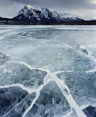 A frozen Abraham Lake in Alberta, Canada, with show capped mountains in the distance. Photographed by Paul Wakefield 2011.