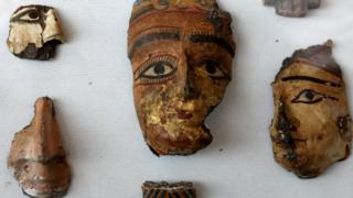 Painted segments of decorative faces at the exposition in the grave