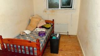 Habitación de la víctima con una cama pequeña y un tacho de basura.