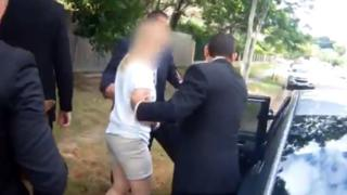 Police officers guide the woman into a car after her arrest