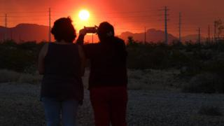 in_pictures A mother and daughter take photos of the fire
