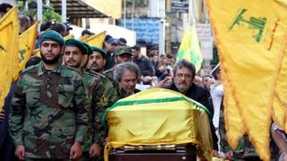 Adnan (C-L) and Hassan Badreddine (C-R), brothers of slain top Hezbollah commander Mustafa Badreddine who was killed in an attack in Syria, mourn next to his casket during the funeral in the Ghobeiry neighbourhood of southern Beirut on 13 May 2016