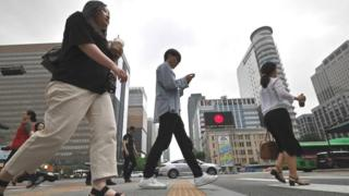 People walk cross a road at a business district in Seoul