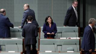 Julia Banks stands to speak in parliament as five male colleagues leave the chamber