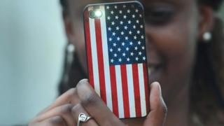 A smartphone in a case showing the US flag