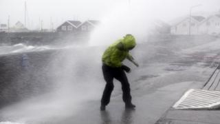 Un résidant de la ville de Bodoe, aux environs du port, se bat dans un temps orageux pour se frayer un chemin (archives)
