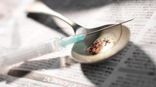 A needle and spoon containing heroin