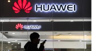 A pedestrian talks on the phone while walking past a Huawei Technologies Co. store on January 29, 2019 in Beijing, China