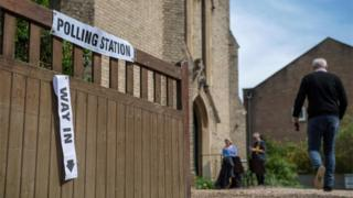 Voters head into a polling station at a church in Twickenham